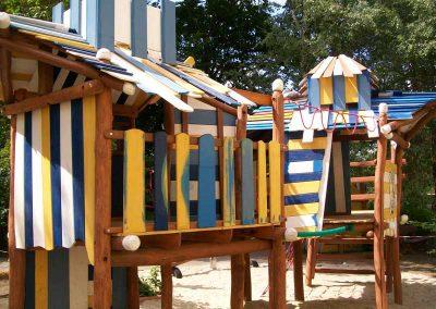 Buntes Spielhaus aus entsplinteten Rundhölzern aus Robinie